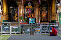 Myanmar, Burma, Yangon.  Sule Pagoda.  Man Praying in front of Buddha Statues, Television Set.  Clear glass recepticals for contributions in front of Buddhas.