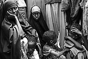 30 year old, Fatima Aden Mohammed from Bardera in the Juba valley, Somalia is seen protecting her 4-year-old daughter Dahira (2nd from left), who has Malaria outside the registration camp in Dagahaley refugee camp in the Dadaab, in northeastern Kenya. Her other 2 year old daughter, Habiba died along the way to the camp. Hundreds of thousands of refugees are fleeing lands in Somalia due to severe drought and arriving in what has become the world's largest refugee camp. Photo: Sanjit Das/Panos