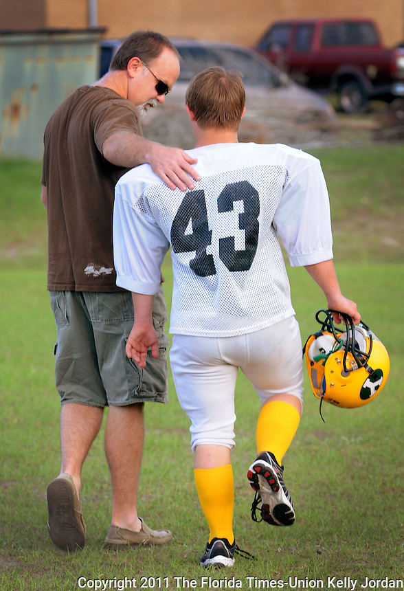"""Kelly.Jordan@jacksonville.com--101211--Yulee football player Jacob """"Jake"""" Martin, right, whose practice number is (43), and game number is (30), walks off of the field with his father Jack Martin following football practice Wednesday October 12, 2011 at Yulee High School. When the Yulee High School football team played a game on one of ESPN's networks, it made Jacob Martin one of the co-captains. Martin, a senior, has Down syndrome and until this season, was a team manager. But this year he is a player who recently got into a game for the final play.(The Florida Times-Union, Kelly Jordan)"""