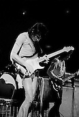 """Chicago, Illinois<br /> July 23, 1975<br /> USA<br /> <br /> Guitarist Ronnie Wood of the Rolling Stones performs live at Chicago Stadium during the band's """"Rolling Stones Tour of the Americas '75"""".<br /> <br /> This was the Stones first tour with new guitarist Ronnie Wood, after Mick Taylor left the band. The Stones, with their usual act freshly aided by theatrical stage props  including a giant inflatable phallus (nicknamed 'Tired Grandfather' by the band, since it sometimes malfunctioned) and, at the Chicago shows, an unfolding lotus flower-shaped stage that Charlie Watts had conceived.<br /> <br /> The band was composed of  Mick Jagger - vocals, guitar, harmonica, Keith Richards - guitar, vocals, Bill Wyman - bass guitar, and Charlie Watts - drums, percussion. <br /> <br /> Additional musicians included: Ronnie Wood - guitar, backing vocals, Ian Stewart - piano, Billy Preston - keyboards, vocals and Ollie Brown - percussion."""