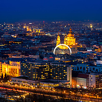 Aerial view from the Royal Palace of the beautiful, lit-up domes of the opera, with the ferris wheel in front, during twilight in Budapest, Hungary