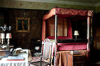 The hand-painted leather-covered walls of this four-poster bedroom are enhanced with a hand-painted decorative frieze