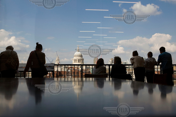Visitors to the Tate Modern art gallery look across the Thames river towards St. Paul's Cathedral.