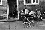 Mrs Carol Backhouse and baby Craig in pram. Snoopy in the doorway.  Northfield estate. South Kirkby.  South Kirkby colliery Yorkshire England. 1979. This is the back of their home.<br />