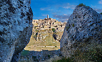 "Long view across ""la Gravina"" ravine to the Sassi of Matera at sunrise, Basilicata, Italy. A UNESCO World Heritage site.<br /> <br /> The area of Matera has been occupied since the Palaeolithic (10th millennium BC) making it one of the oldest continually inhabited settlements in the world. <br /> The town of Matera was founded by the Roman Lucius Caecilius Metellus in 251 BC and remained a Roman town until  was conquered by the Lombards In AD 664 becoming part of the Duchy of Benevento.  Matera was subject to the power struggles of southern Italy coming under the rule of the Byzantine Roman, the Germans and finally Matera was ruled by the Normans from 1043 until the Aragonese took possession in the 15th century. <br /> <br /> At the ancient heart of Matera are cave dwellings known as Sassi. As the fortunes of Matera failed the sassy became slum dwelling and the appalling living conditions became be the disgrace of Italy. From the 1970's families were forcibly removed from the Sassi and rehoused in the new town of Matera. Today tourism has regenerated Matera and the sassi have been modernised and are lived in again making them probably the longest inhabited houses in the world dating back 9000 years."