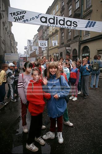Krakow, Poland. Group of school children; Adidas advert; shopping street.