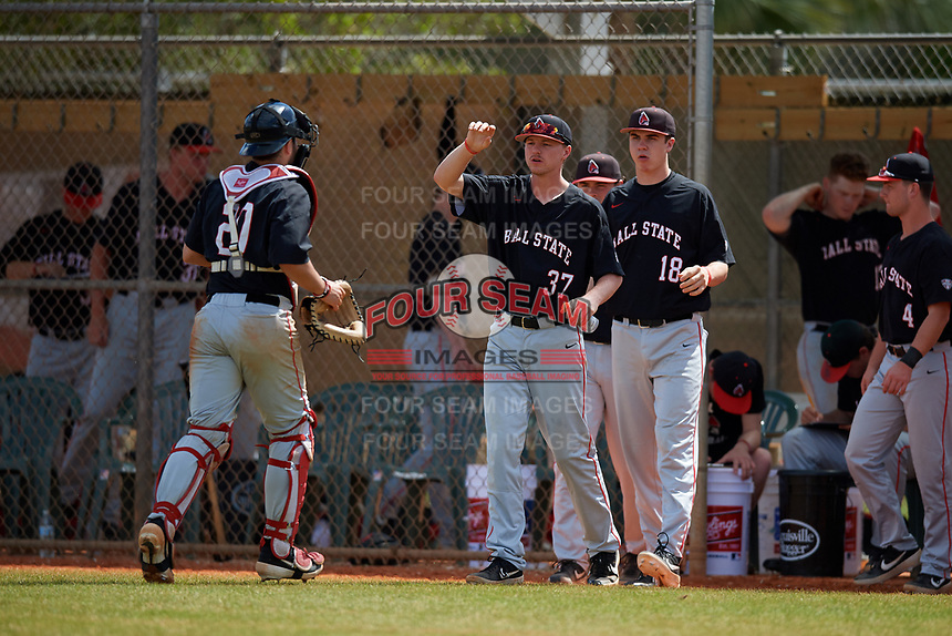 Ball State Cardinals Lukas Jaksich (37) and Zach Losey (18) greet catcher Chase Sebby (20) during a game against the Saint Joseph's Hawks on March 9, 2019 at North Charlotte Regional Park in Port Charlotte, Florida.  Ball State defeated Saint Joseph's 7-5.  (Mike Janes/Four Seam Images)