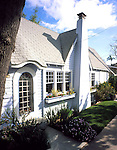 San Diego, California. 1925-1926.  This diminutive cottage is a charmer with its mullioned, arched glass front door, window boxes beneath six over six, double hung windows, prominent chimney bisecting the front gable as if it were a grand, English manor house, and varied roofline complete with an eyebrow arch and a steep, but tiny gable.  Built by Frank Melcher, a local builder and realtor, the cottage has been the starter home for many young families, from teachers to Navy seamen, who however often outgrew its cottage proportions and moved on to larger homes.  Many of the original interior details luckily remain intact, from blue and white, hexagonal tiles in the bathroom to a niche above the fireplace for a special piece of pottery.  One of the more unusual features which still remains is a drawer bed in the living room.  A large drawer pulls out to reveal a three-fourths size bed; the bed tucks up into a walk-in closet in the bathroom when not in use.<br /> RELEASED
