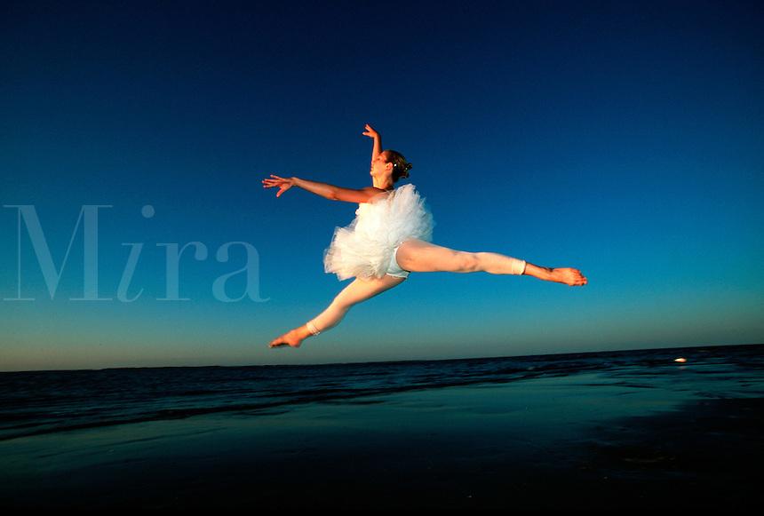 Ballet dancer jumps during sunset dance at the beach.