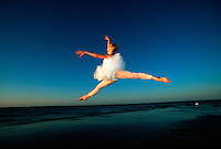 Ballet dancer jumps during sunset dance at the beach.