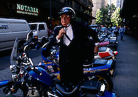 Chilean businessman parks his motorcycle with many other commuters. Businessmen negotiate through heavy traffic on motorcycles parking them on a street near the financial district of Chile's capital city.