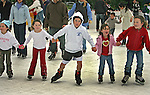 The Maguire family (L-R) Danielle (6), Therese (5), Gerald (8) and Victoria (3), far right (no name) join hands on ice where they where a part of the hundreds of people at the Embarcadero Center to ice skate at the Holiday ice rink in San Francisco, California.