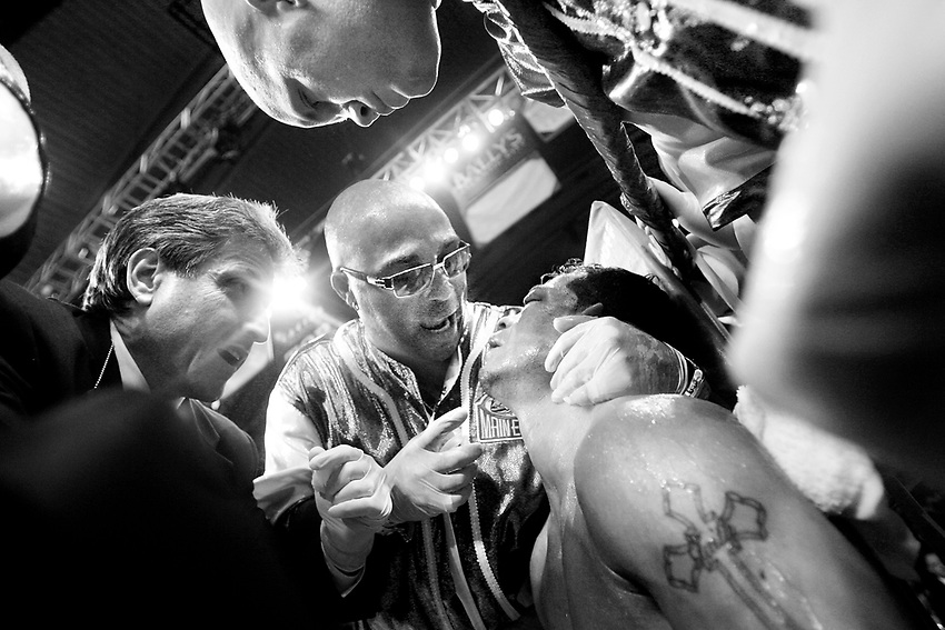 """ARTURO GATTI (10/12) --Arturo stumbled back to his corner after somehow surviving a vicious beating in the sixth round, trainer Buddy McGirt (center) tells the champ he's going to stop the fight. Gatti, at first pleads to go one more round, but finally looks up and relents, saying to McGirt, """"OK. I trust you coach."""" .The fight was over.  ATLANTIC CITY, NJ  6/25/05"""