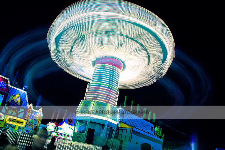 A slower shutter speed (2.0 sec) renders the whirling children on this carnival ride into circular trails of light at the Montgomery County Agricultural Fair in Gaithersburg, Maryland.