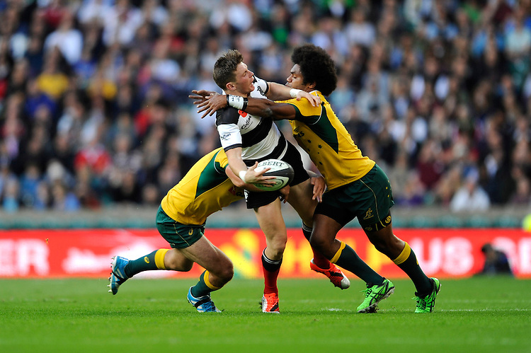 Colin Slade of Barbarians offloads as he is tackled by Henry Speight (r) and Matt Hodgson of Australia during the Killik Cup match between Barbarians and Australia at Twickenham Stadium on Saturday 1st November 2014 (Photo by Rob Munro)