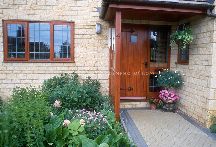 Pretty front entryway of stone house, with wind chimes, stone pathway, container plants of annual flowers, hanging plants, foundation gardening perennial beds, covered doorway, peonies and perennial geraniums