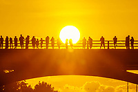 Beautiful sunset paints the Congress Avenue Bridge while bat watchers stand in silhouette waiting for the bats to take flight in downtown Austin, Texas.