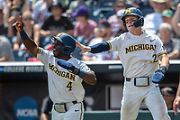 Michigan Wolverines second baseman Ako Thomas (4) celebrates with teammate Jack Blomgren (2) after scoring against the Texas Tech Red Raiders in the NCAA College World Series on June 21, 2019 at TD Ameritrade Park in Omaha, Nebraska. Michigan defeated Texas Tech 15-3 and will play in the CWS Finals. (Andrew Woolley/Four Seam Images)