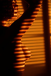 Artistic nude photo of a topless woman standing in light coming through window blinds leaving a stripy pattern on the outline of her breast Image © MaximImages, License at https://www.maximimages.com