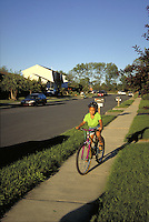 African-american girl riding bike in suburb.