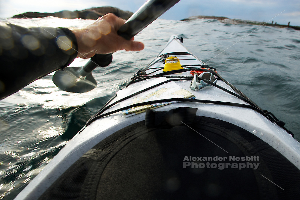 USA, Little Compton, RI - First Person point of view Kayak paddles in open water toward rocks.  Deck is well equipped with compass, chart, water bottle, and sunglasses.