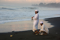 """Priests make an offering to the spirits during the Melasti Ceremony on Purnami Beach, Bali, Indonesia.<br /> Available as Fine Art Print in the following sizes:<br /> 08""""x12""""US$   100.00<br /> 10""""x15""""US$ 150.00<br /> 12""""x18""""US$ 200.00<br /> 16""""x24""""US$ 300.00<br /> 20""""x30""""US$ 500.00"""