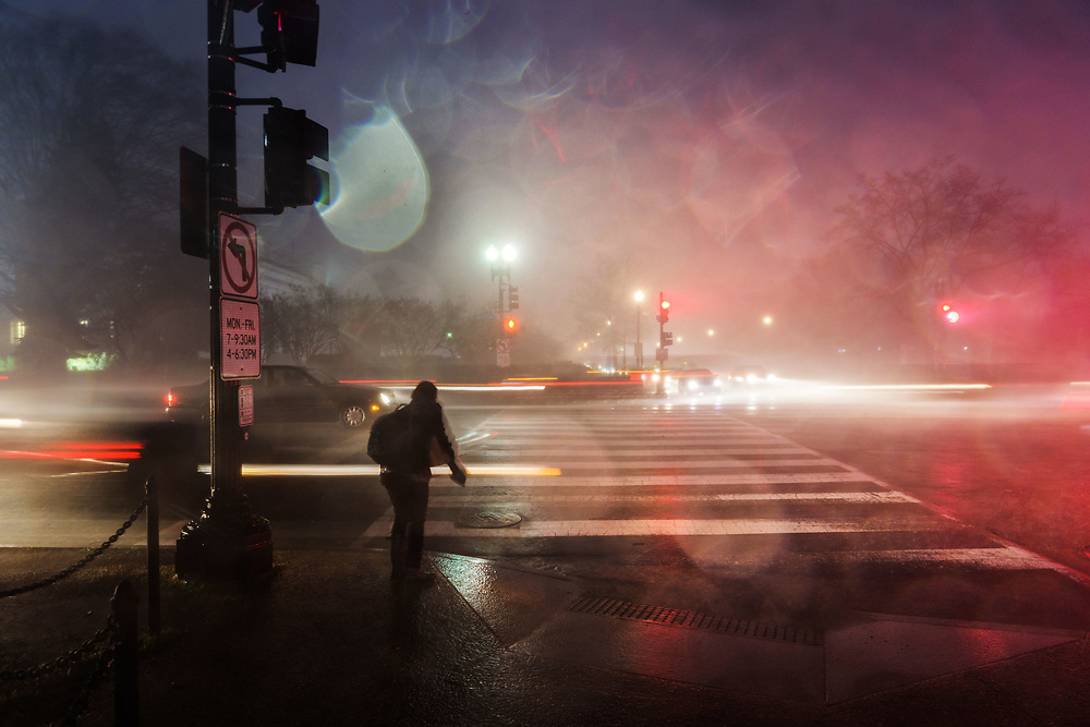 A pedestrian waits for the walking signal on Constitution Avenue and 17th Street at the onset of a downpour from passing storms over Washington DC.