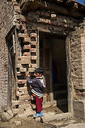 (Alison Griffin to fill in names) (Name)'s youngest son hugs a brick at the entrance to his three storied house that was severely damaged during the floods in September in Abikarpora village on the Dal Lake, Srinagar, Jammu and Kashmir, India, as seen here on 25th March 2015. Since the flood, she has been widowed, and is left with four young children and no home. Her family now lives in a temporary shelter built using the emergency shelter kit, and continues their recovery with the help of relief kits such as education kit, food basket, hygiene kit and non-food items from Save the Children. Photo by Suzanne Lee for Save the Children