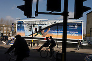 Peckham locals and a Visa advertising billboard featuring the arm of Olympic athlete Usain Bolt in south London.
