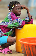 A girl waits to fill a container during a UNICEF-sponsored drinking water distribution to flood victims in Cotonou, Benin on Sunday October 24, 2010. The city's water network has been rendered unusable in flooded parts of the city, and many people rely on such water distributions that are carried out by the fire service..