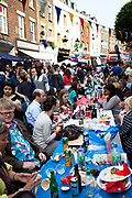 Eating and drinking on long communal tables at a street party on Battersea High Street to celebrate the Royal Wedding of Prince William and Kate Middleton, April 29th 2011. Thousands attended this one of the largest street parties in London. Embracing the diversity of the community, the theme of the party is world food, dance and music, with live coverage of the royal Wedding aired on a giant screen.