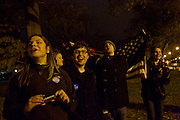 George Washington University students Hannah Flom, from left, Shanna Helf, Zach Montellaro, Tim Stackhouse and Laura Longman, all 18, look down 15th Street NW in Washington, D.C. to catch a glimpse of President Barack Obama's motorcade as he returned to Washington from Chicago on Wednesday evening. Each of the students voted for the first time in this year's eleciton.