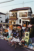 The Ukita family's possessions displayed in front of their house before the family photograph for the Material World project. The family is situated on the two balconies of the upstairs bedrooms for this preliminary photograph. The Ukita family lives in a 1421 square foot wooden frame house in a suburb northwest of Tokyo, Japan, called Kodaira City. Material World Project.