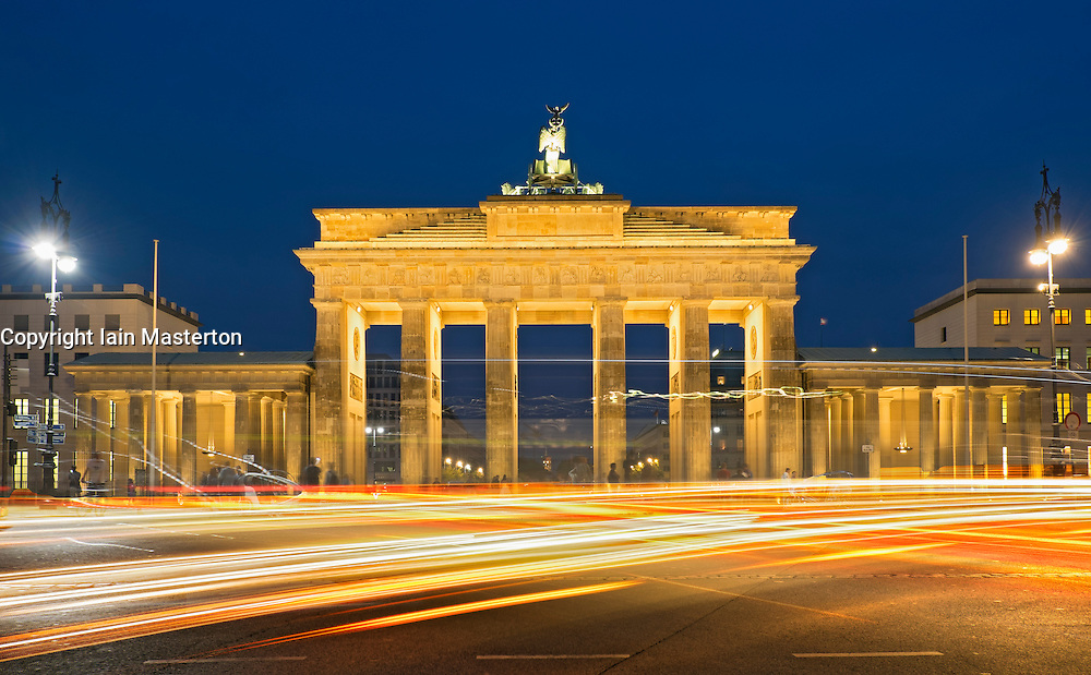 Long exposure traffic light trails in front of Brandenburg Gate at night in Berlin Germany