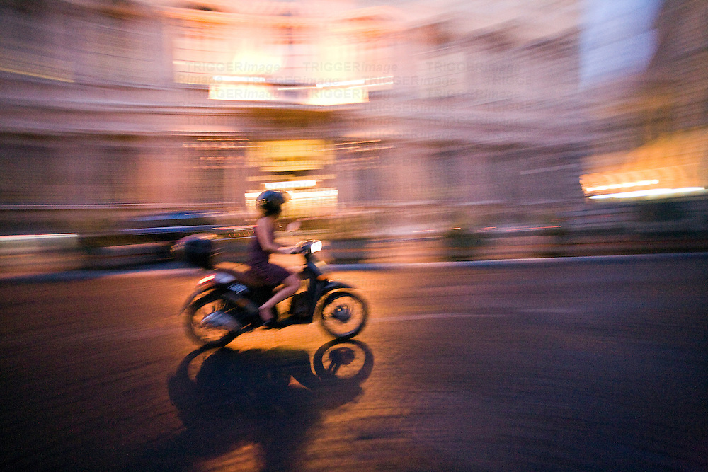 Panning shot of typical Roman scooter in Italy ridden by young female