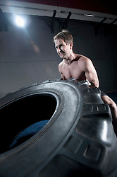 Man training with tractor wheel in gym by pushing, Bavaria, Germany