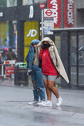 © Licensed to London News Pictures. 30/07/2021. LONDON, UK.  People in Oxford Street experience windy and rainy conditions as Storm Evert passes across the capital. Yellow warnings for wind and thunderstorms are in place across the east and south-east of England..  Photo credit: Stephen Chung/LNP