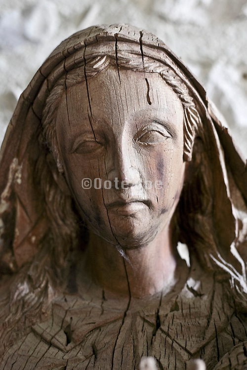 old dried out splitting wood portrait sculpture of the religious figure Maria