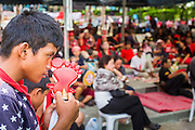 01 MAY 2013 - BANGKOK, THAILAND:   A teen aged Thai Red Shirt scratches his nose with a Red Shirt noise clapper during the Red Shirt rally and protest at the Constitutional Court in Bangkok. Several hundred Thai Red Shirts, members of the United Front for Democracy against Dictatorship (UDD), have been camped out at Thailand's Constitutional Court, which oversees matters related to the Thai constitution and constitutional amendment. The Red Shirts are protesting the court's decision to consider a petition regarding the constitutionality of the constitutional amendments that have been proposed by the government. The group is arguing that by considering the petition, the Court is impeding the powers of the legislative branch. PHOTO BY JACK KURTZ