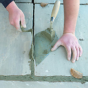 A member of the maintenance department concretes between paving slabs using a trowel, Newby Hall estate and gardens, Ripon, North Yorkshire, UK