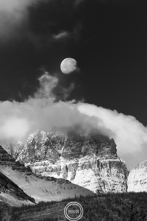 The moon sets over the peaks of Glacier National Park.