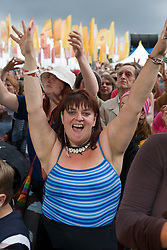 Young woman in a crowd cheering band of musicians on stage at the WOMAD (World of Music; Arts and Dance) Festival in reading; 2005,
