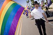 14 APRIL 2007 -- PHOENIX, AZ: A man carries the Gay Pride flag at the annual Gay Pride Parade in Phoenix, AZ.  Photo by Jack Kurtz