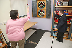 Woman with scoliosis - curvature of the spine - playing darts watched by man with CP - cerebral palsy - at a resource for people with physical and sensory impairment.