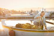 Fisherman checking fishing net on boat moored in harbor at sunrise, Skala Kallonis, Lesbos, Greece