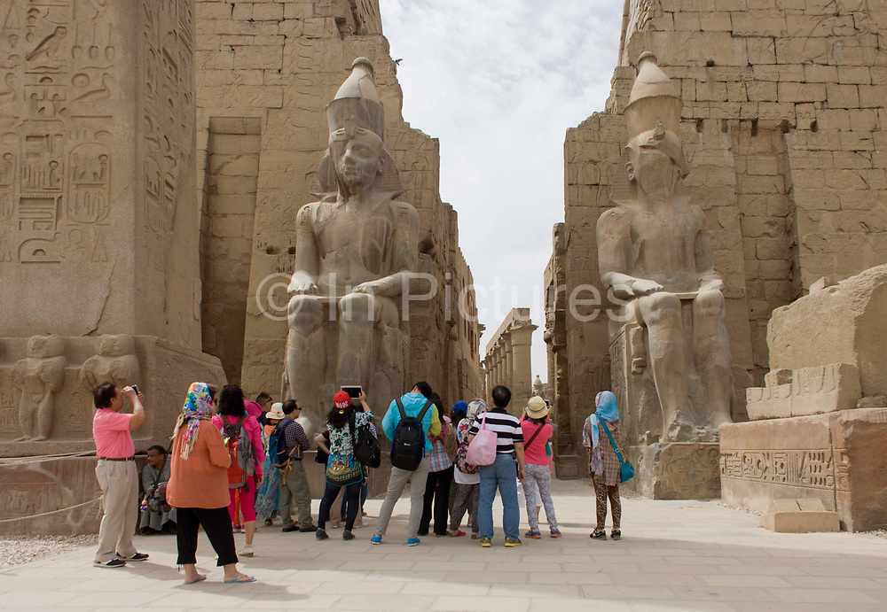Tourist groups stand and photograph beneath the giant colossi at the entrance of the ancient Egyptian Luxor Temple, Nile Valley, Egypt. According to the country's Ministry of Tourism, European visitors to Egypt is down by up to 80% in 2016 from the suspension of flights after the downing of the Russian airliner in Oct 2015. Euro-tourism accounts for 27% of the total flow and in total, tourism accounts for 11.3% of Egypt's GDP. The temple was built by Amenhotep III, completed by Tutankhamun then added to by Rameses II. Towards the rear is a granite shrine dedicated to Alexander the Great and in another part, was a Roman encampment. The temple has been in almost continuous use as a place of worship right up to the present day.