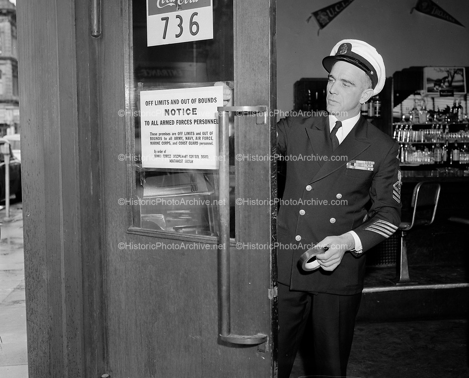 """Y-570312-02.  Harbor Club, SW 1st & Yamhill, Van Rensselaer Building, Naval officer attaching sign to door """"Off limits and out of bounds to all military personnel"""". March 12, 1957"""
