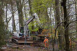 HS2 workers observe a large mechanical digger being used for the 'translocation' of soil in ancient woodland at Jones Hill Wood in the Chilterns AONB on 28th April 2021 in Wendover, United Kingdom. Soil translocation is intended to be an environmental mitigation measure for the HS2 high-speed rail link. Felling of Jones Hill Wood, which contains resting places and/or breeding sites for pipistrelle, barbastelle, noctule, brown long-eared and natterer's bats and is said to have inspired Roald Dahl's Fantastic Mr Fox, has recommenced after a High Court judge yesterday refused environmental campaigner Mark Keir permission to apply for judicial review and lifted an injunction on felling for the rail infrastructure project.