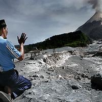 Indonesie.Jogjakarta.Juni 2006.<br /> Hulpverleners en locale mensen uit het natuurrampgebied rond Jogjakarta helpen mee de weg vrij te maken van lagen vulkaanas as gevolg van de recente vulkaanuitbarsting.<br /> Op de foto een plaatselijke bewoner vraagt temidden van de lawine vulkaanas van 1 week geleden de vulkaan de Merapi om vergiffenis en probeert de vulkaan gunstig te stemmen.<br /> Foto:Jean-Pierre Jans