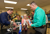 Sgt. Det Chris Jacques and Chief Tony Bean Burpee help with sprinkles and whipped cream on Emily Watson and Lauren Gallant's ice cream sundaes during the Gilford Middle School 5th grade D.A.R.E. program on Thursday morning.  (Karen Bobotas/for the Laconia Daily Sun)